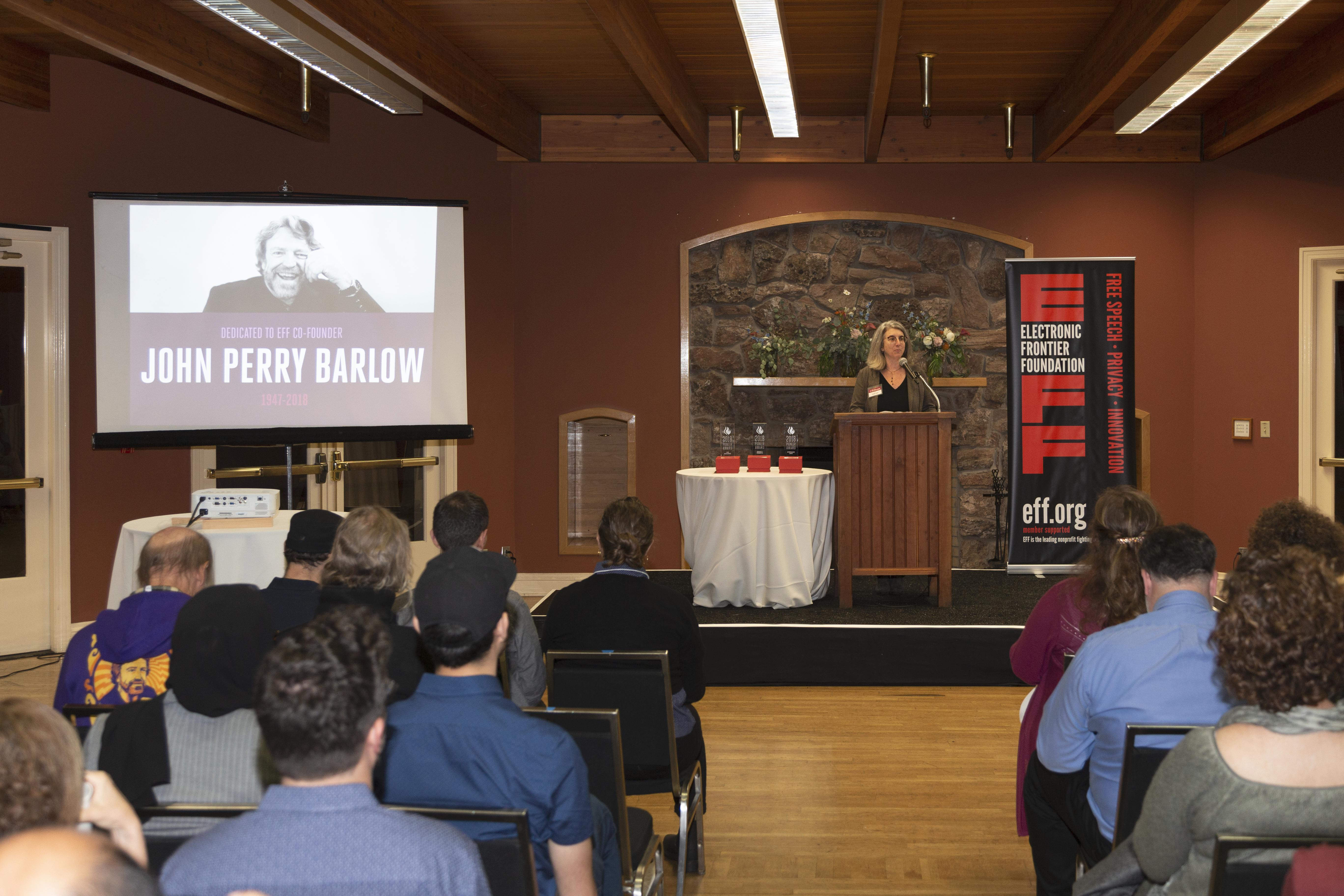 Picture of screen and raised dias with podium. To the left, is a projected image of our co-founder, John Perry Barlow. At the poduim on the right is our Executive Director Cindy Cohn, opening the