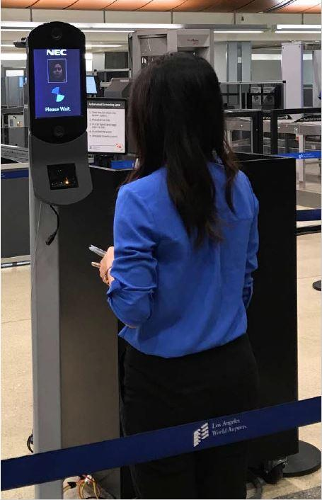 A woman stands facing a small screen that's about five feet off the ground on a pedestal. This is an example of a face recognition kiosk from TSA's website.