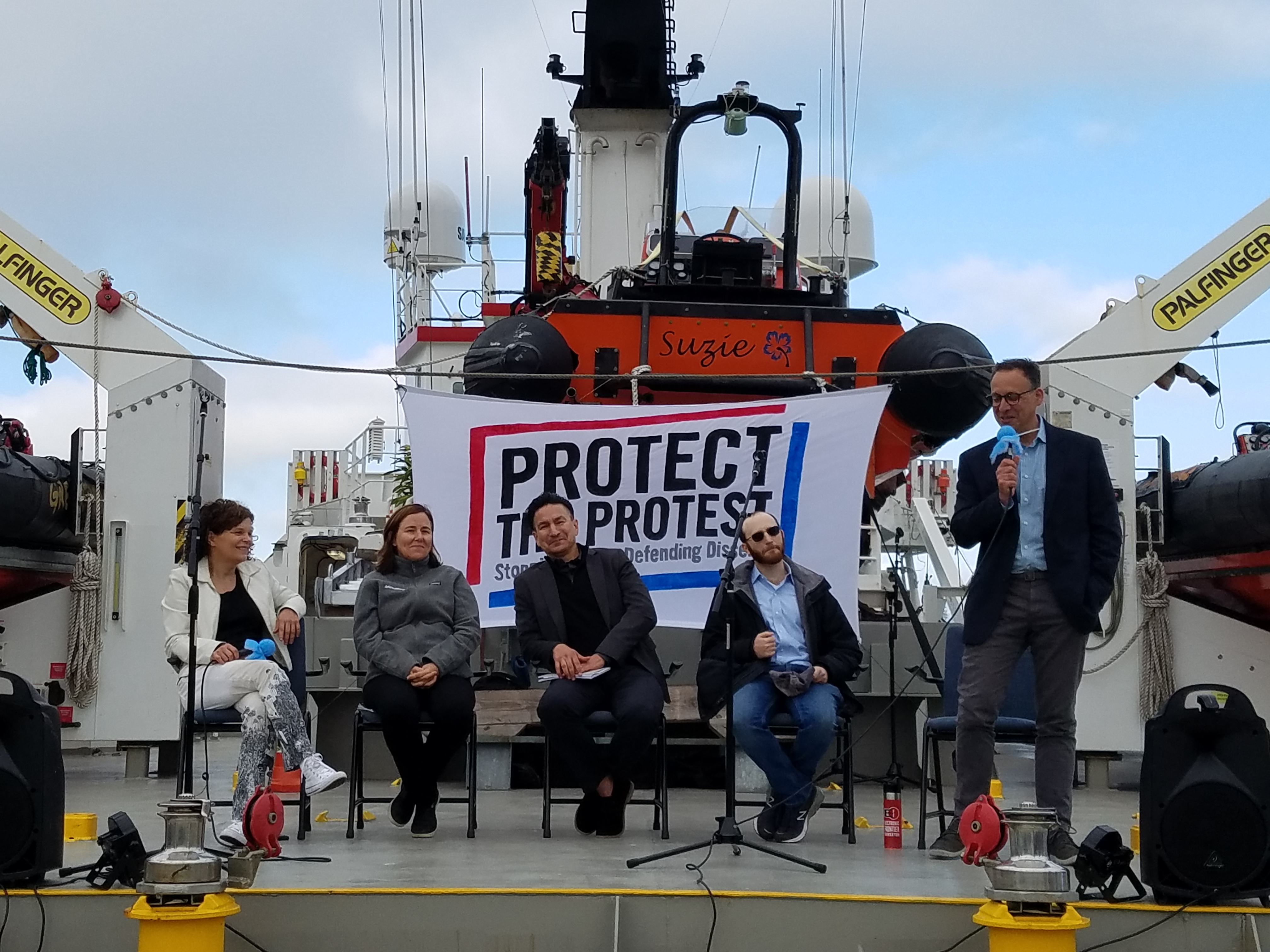 "Aboard a ship that is carrying three smaller boats, four people face an audience to discuss their civil liberties work. A banner that says ""Protect the Protest"" hangs behind the speakers."