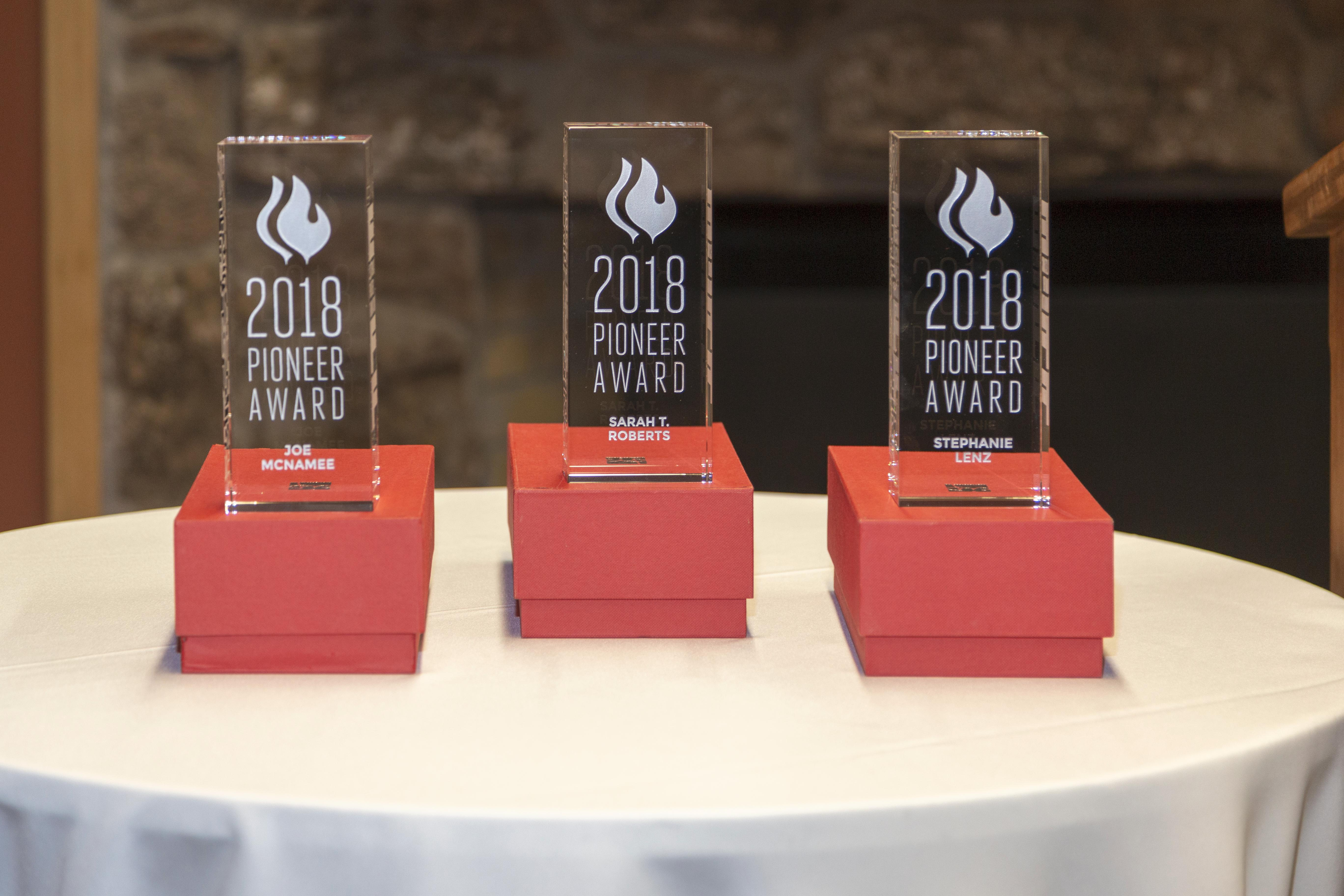 "Three 9"" by 3"" by 2"" rectangular awards in clear acrylic. Front engraved with ""2018 Pioneer Award"" and ""Joe McNamee"", ""Sarah T. Roberts"" and ""Stephanie Lenz"", respectively."