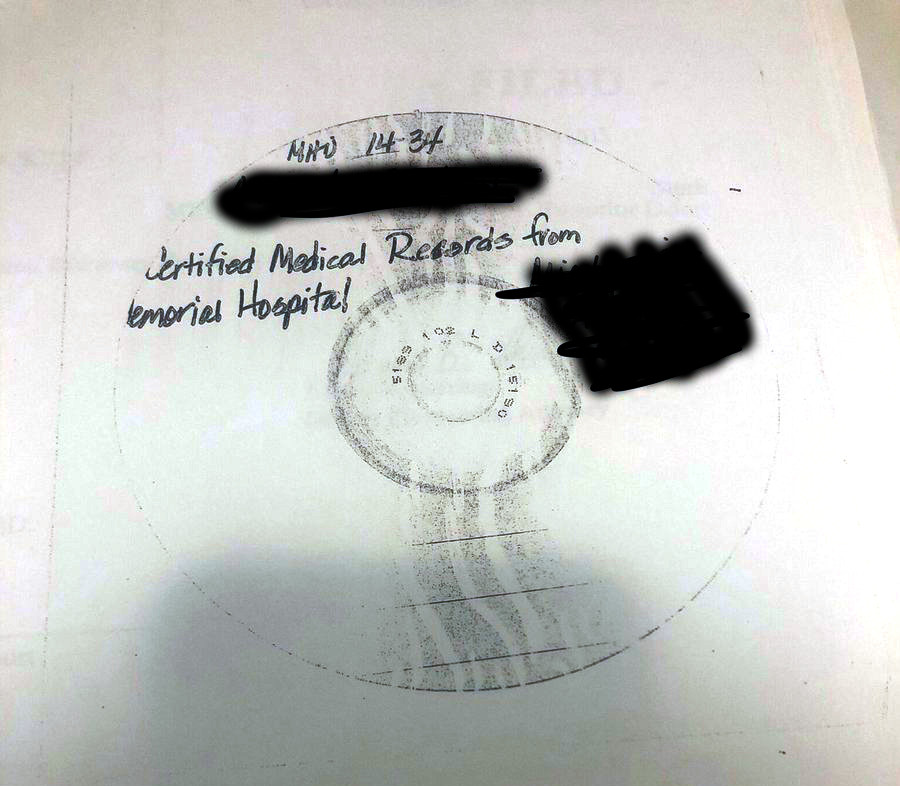 A photocopy of a CD with personal information blacked out