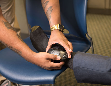 An image shows someone being fitted with an ankle bracelet electronic monitoring device.