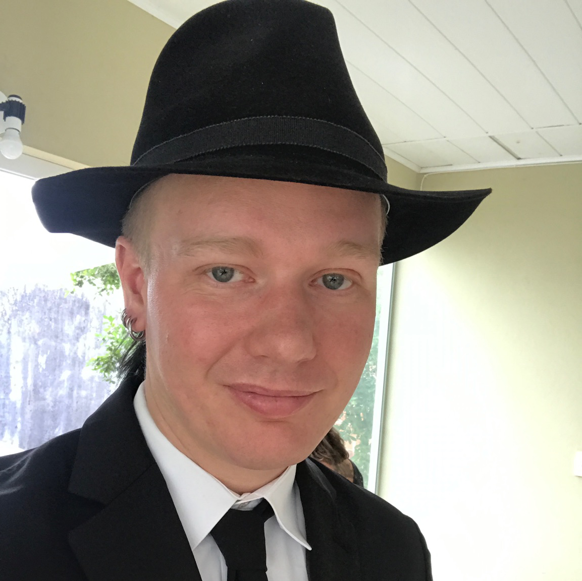 A picture of ola bini. The picture shows a young man in a suit and tie, wearing a black hat.