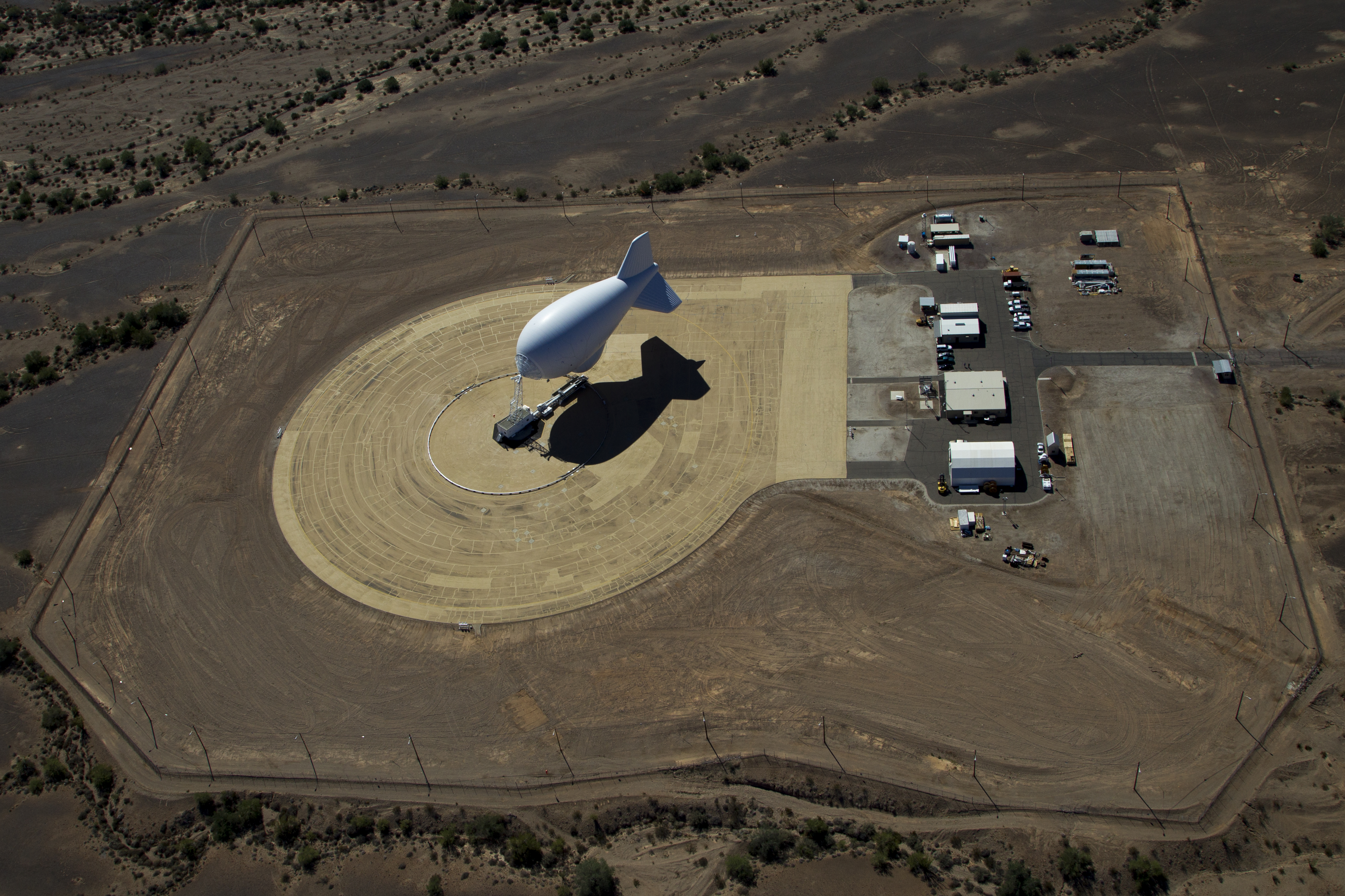 A blimp-shaped surveillance balloon is moored in an open space.