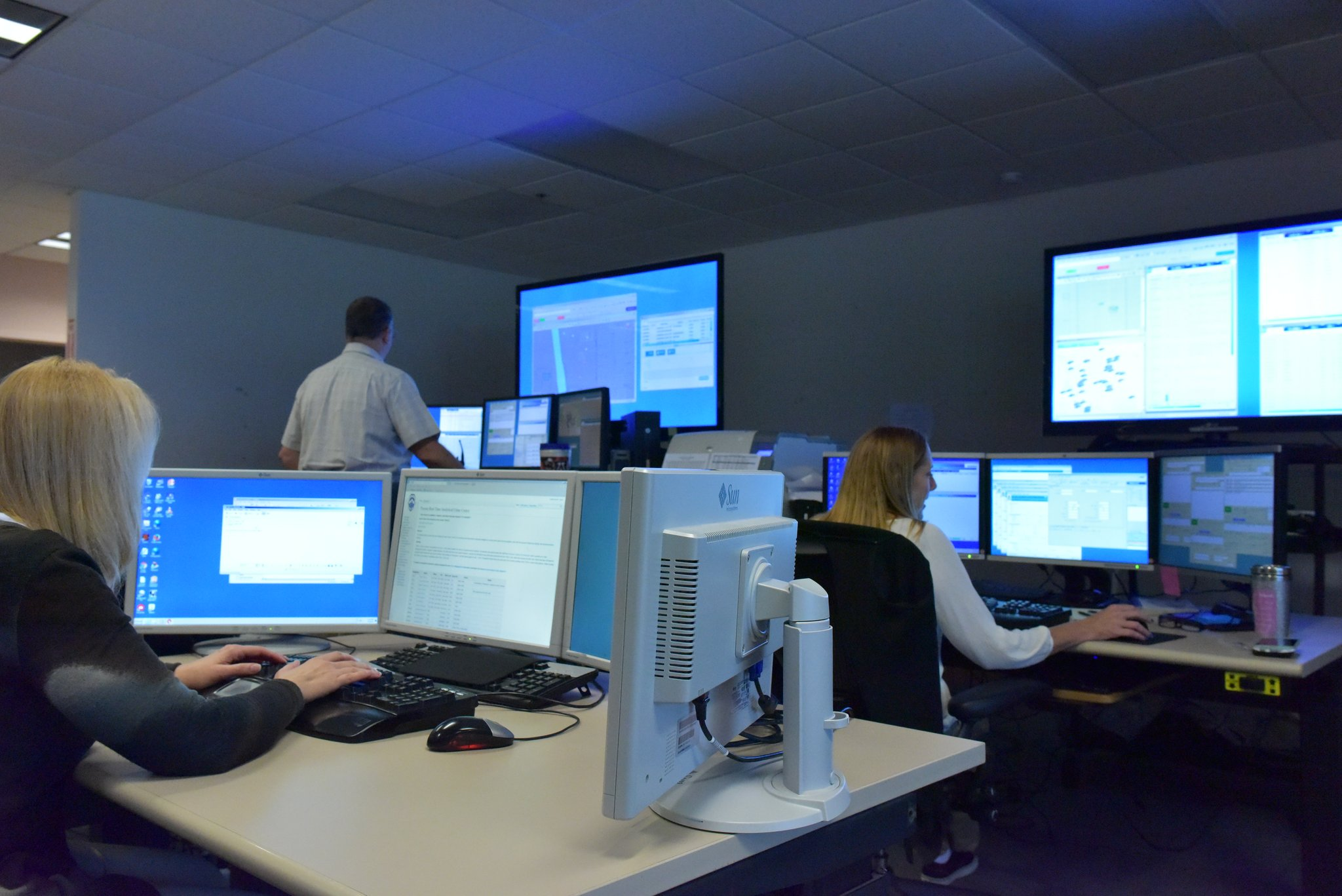 Tucson Police staff sit at work stations, each with multiple computer monitors.