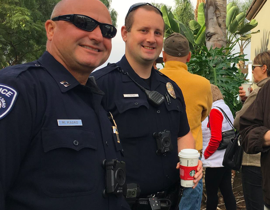 Two police officers drinking coffee while wearing body-worn cameras