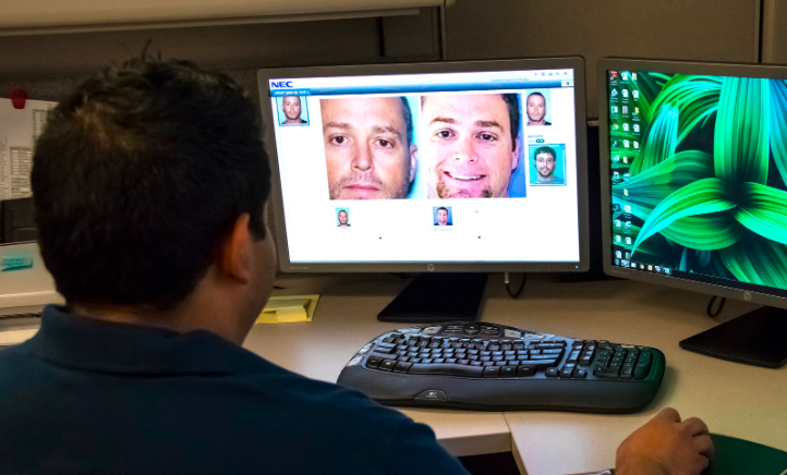 A police office sits at a computer comparing two mugshots with NEC software.