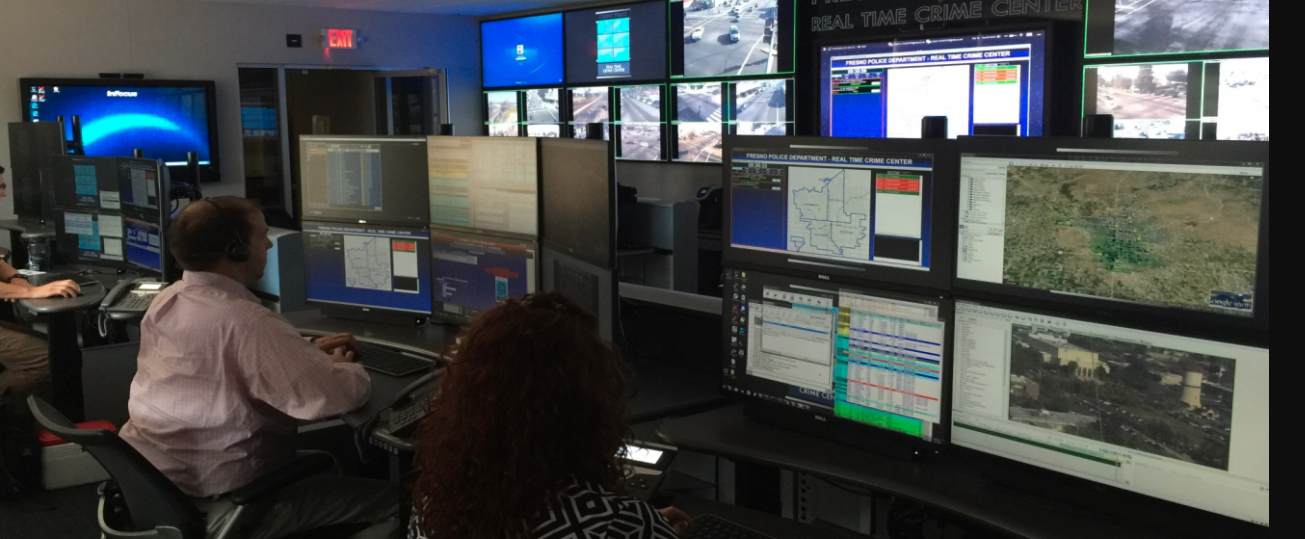 Several analysts sitting at work stations in the Fresno Real-Time Crime Center