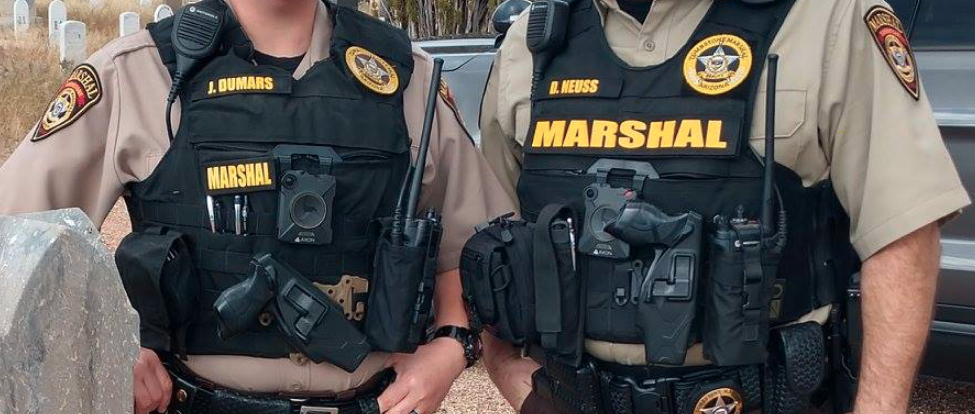 Two armed Tombstone Marshals with square Axon body-worn cameras in the center of their vests.