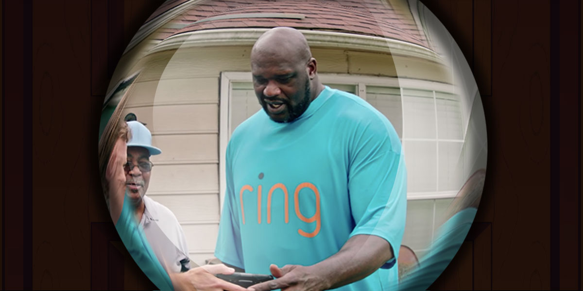 Shaq endorsing Ring with some people, as viewed through a peephole