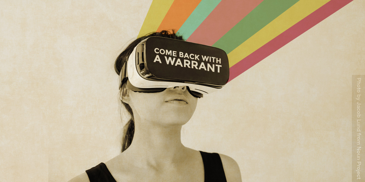 """Person wearing a VR headset on which text reads """"Come back with a Warrant""""."""