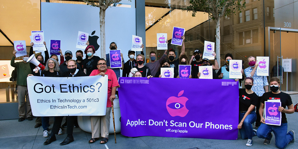 25 people holding banners in front of an apple store