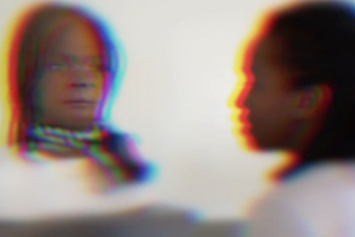 Distorted image of what appears to be a person looking into a mirror. However, instead of their image what appears to be a human-like robot is reflected.