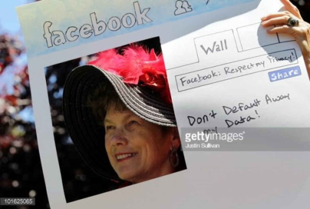 Photo of a Woman in a large hat with feathers, holding a protest sign asking Facebook not to give away users privacy by default