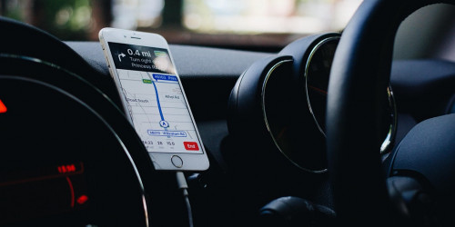 image of an iphone mounted on a car dashboard, with a map application on the screen