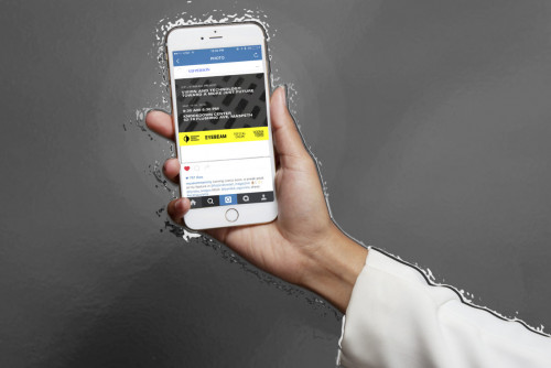 Over a gray background, a hand holds a mobile device displaying event details for Vision and Technology: Toward a More Just Future