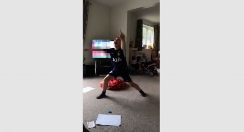 Child dancing in front of blurred television