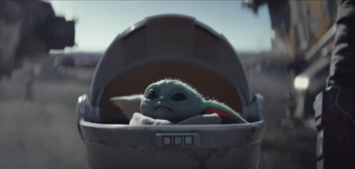 A tiny green baby yoda in a floating bassinet